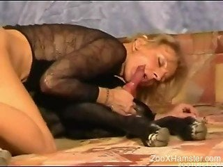 Blond-haired beauty riding a black dog's huge cock
